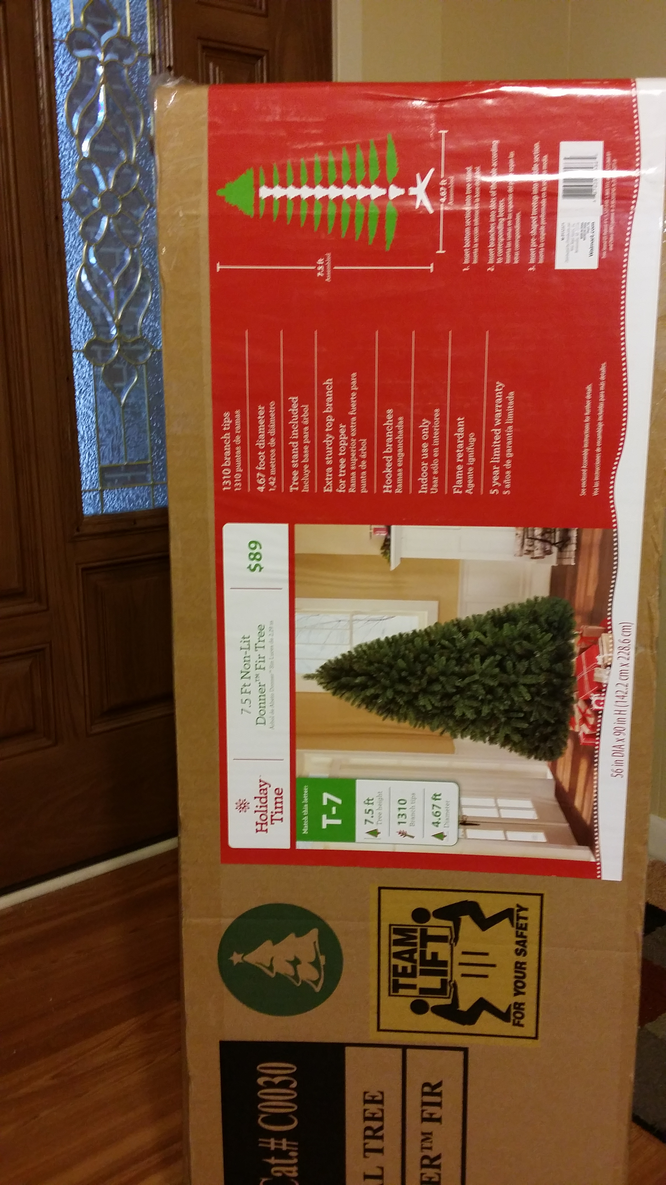 Putting up the christmas tree man style holding for Christmas tree in a box